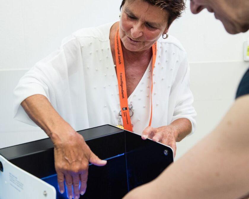 Eine Frau zeigt einer Patientin wie das neue Desinfektionsgerät mit UV funktioniert