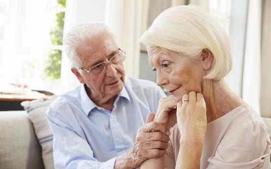 Ein älterer Mann unterstützt seine Frau
