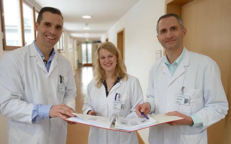 Zwei Ärzte und eine Ärztin halten einen Ordner und lächeln in die Kamera