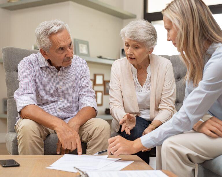 Älteres Paar in einer Besprechung mit einer Frau.