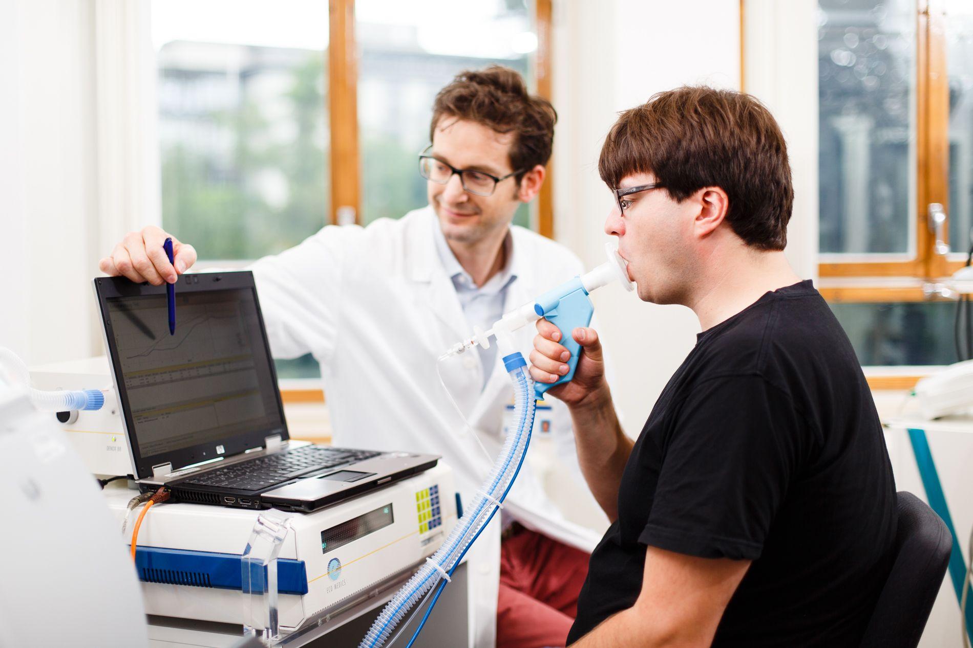 Ein Arzt erklärt einem Patienten, der gerade einen Lungenfunktionstest macht, wie Auswertung zu verstehen ist