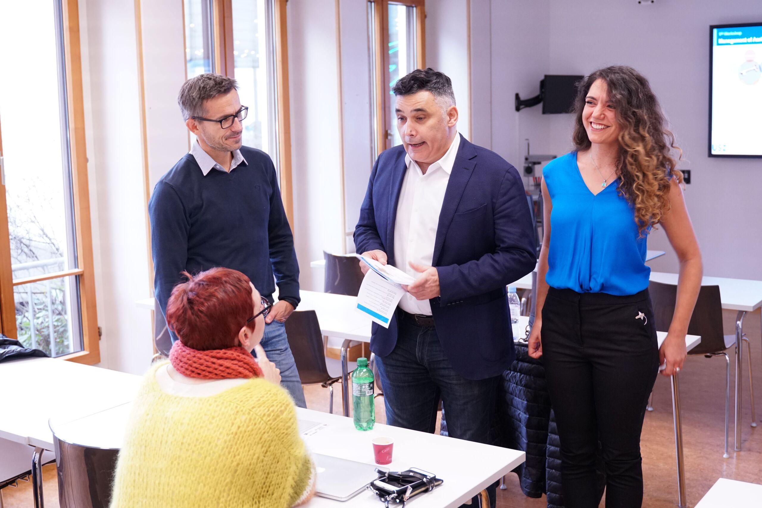 Drei Personen stehen vor einer sitzenden Frau, wobei ein Mann mit ihr redet