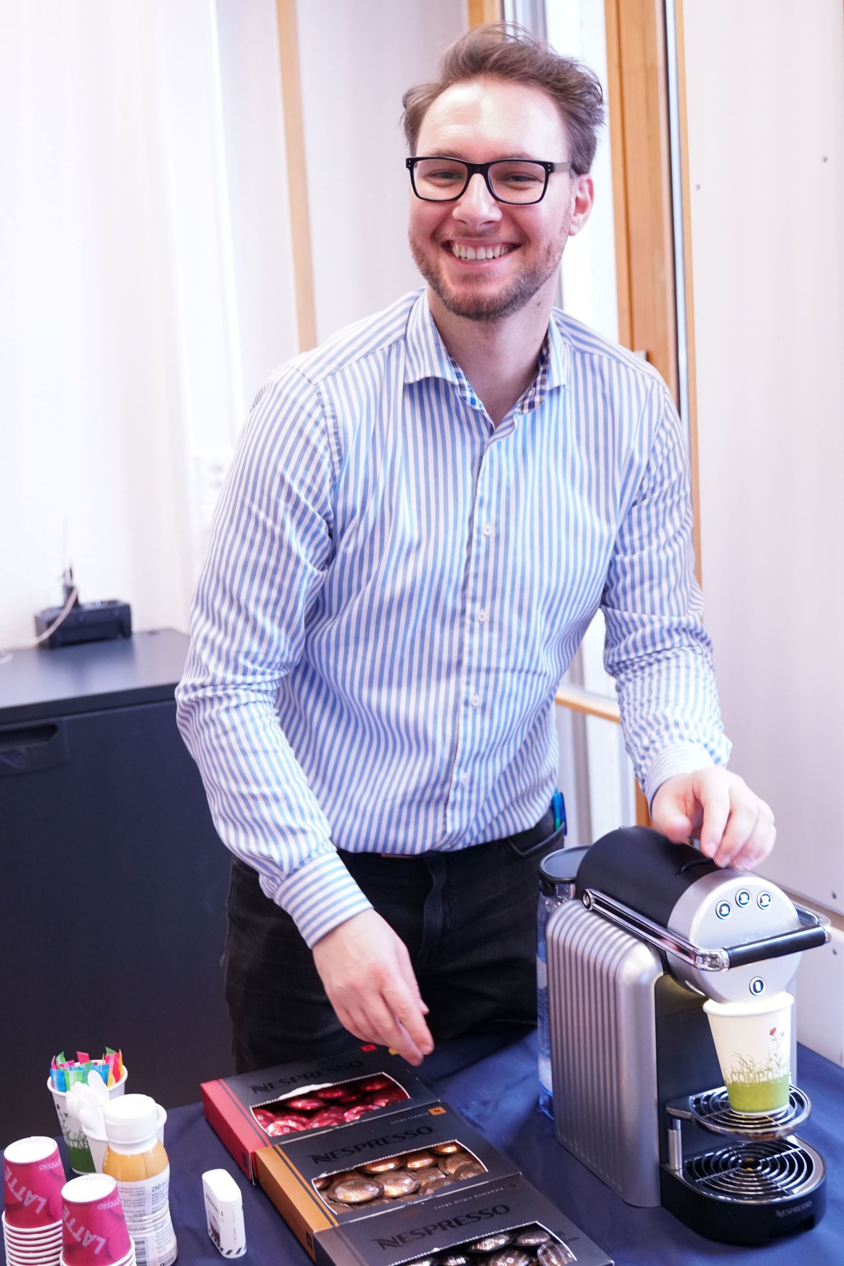 Mann steht lächelnd hinter einer Nespresso Maschine