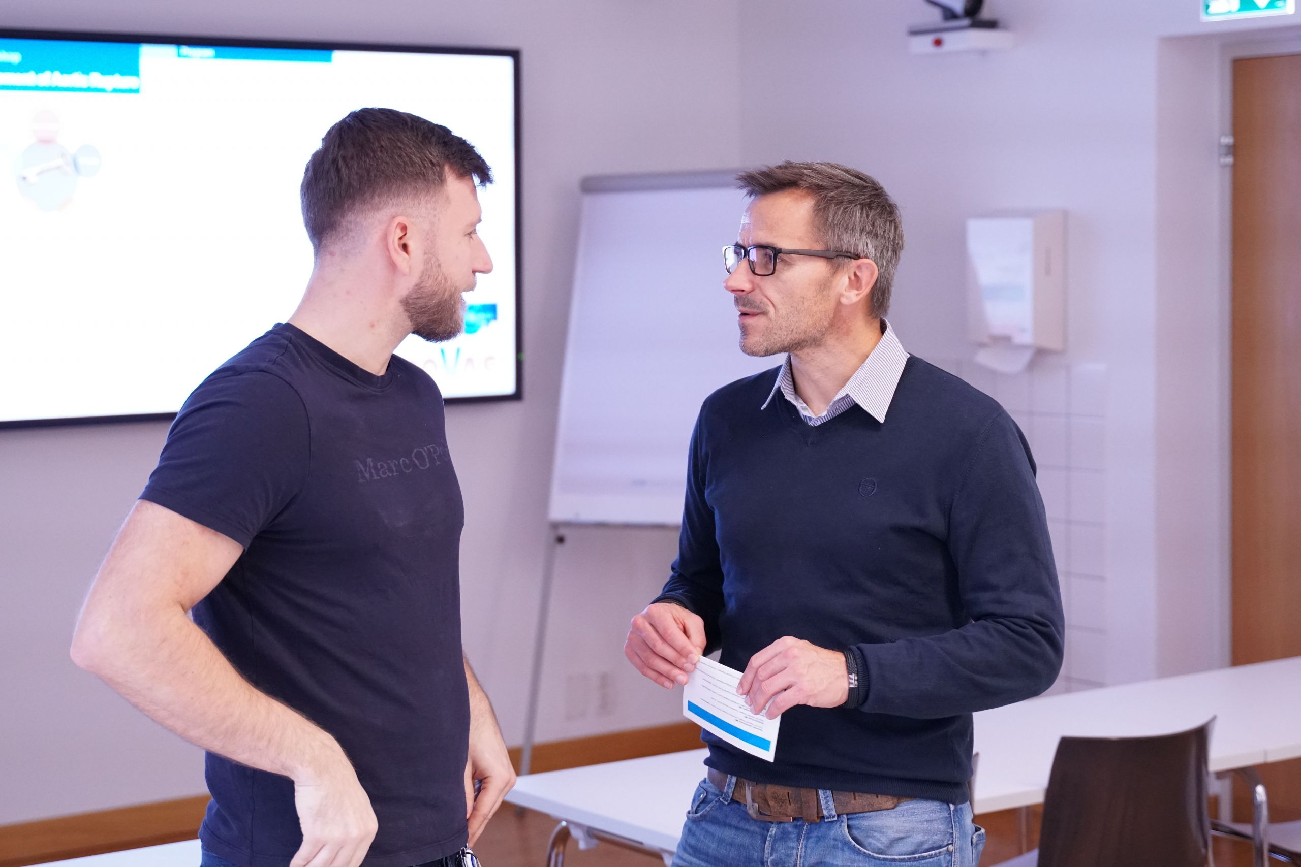Zwei Männer diskutieren etwas in einem Präsentationsraum