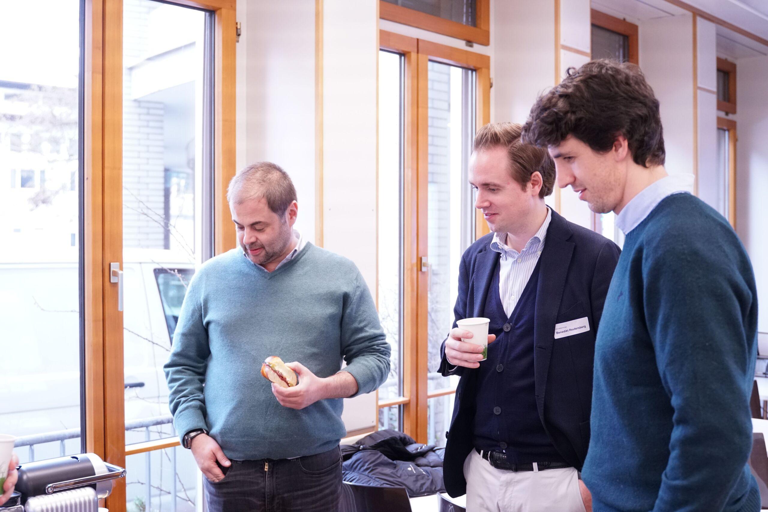 Drei Männer stehen vor einer Kaffeemaschine und warten