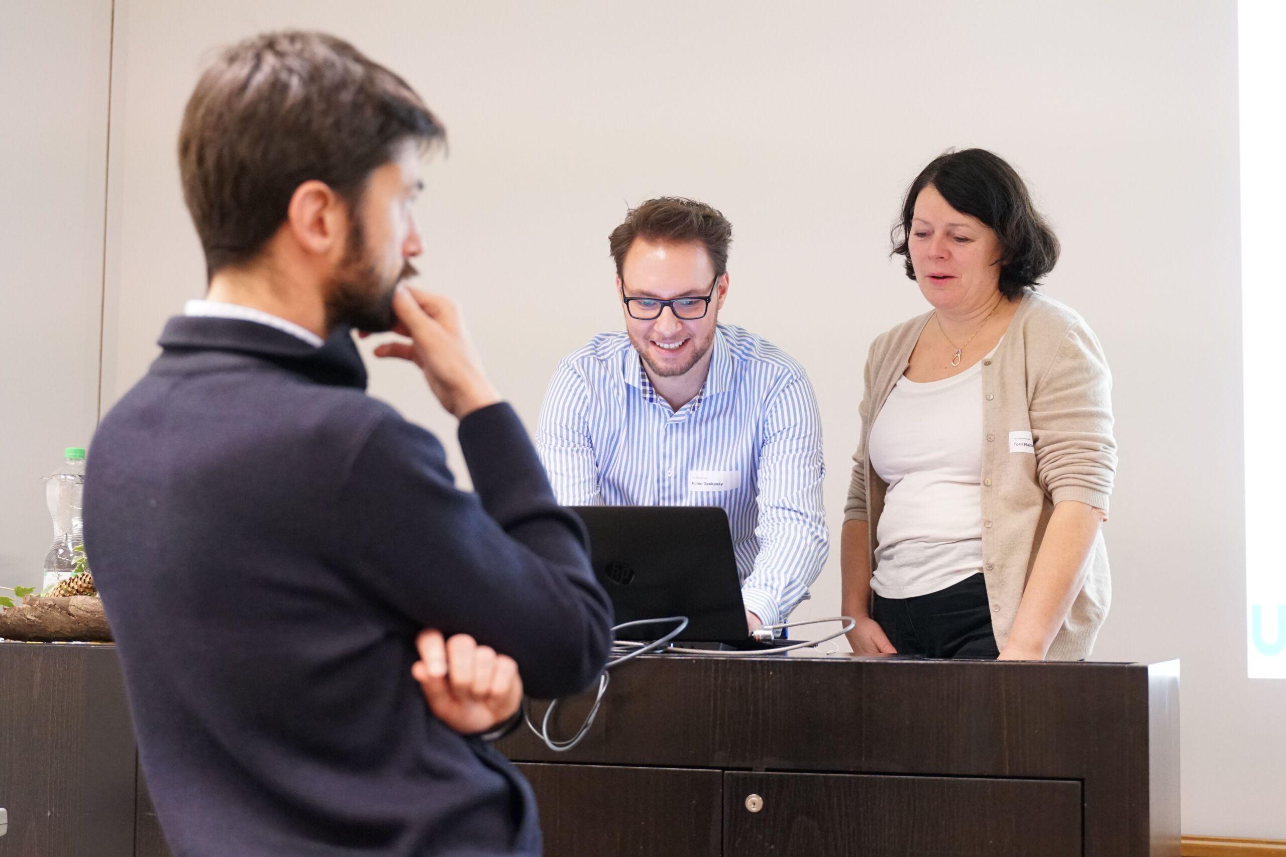 Ein Mann schaut interessiert eine Präsentation an, während zwei Personen an einem Laptop sind
