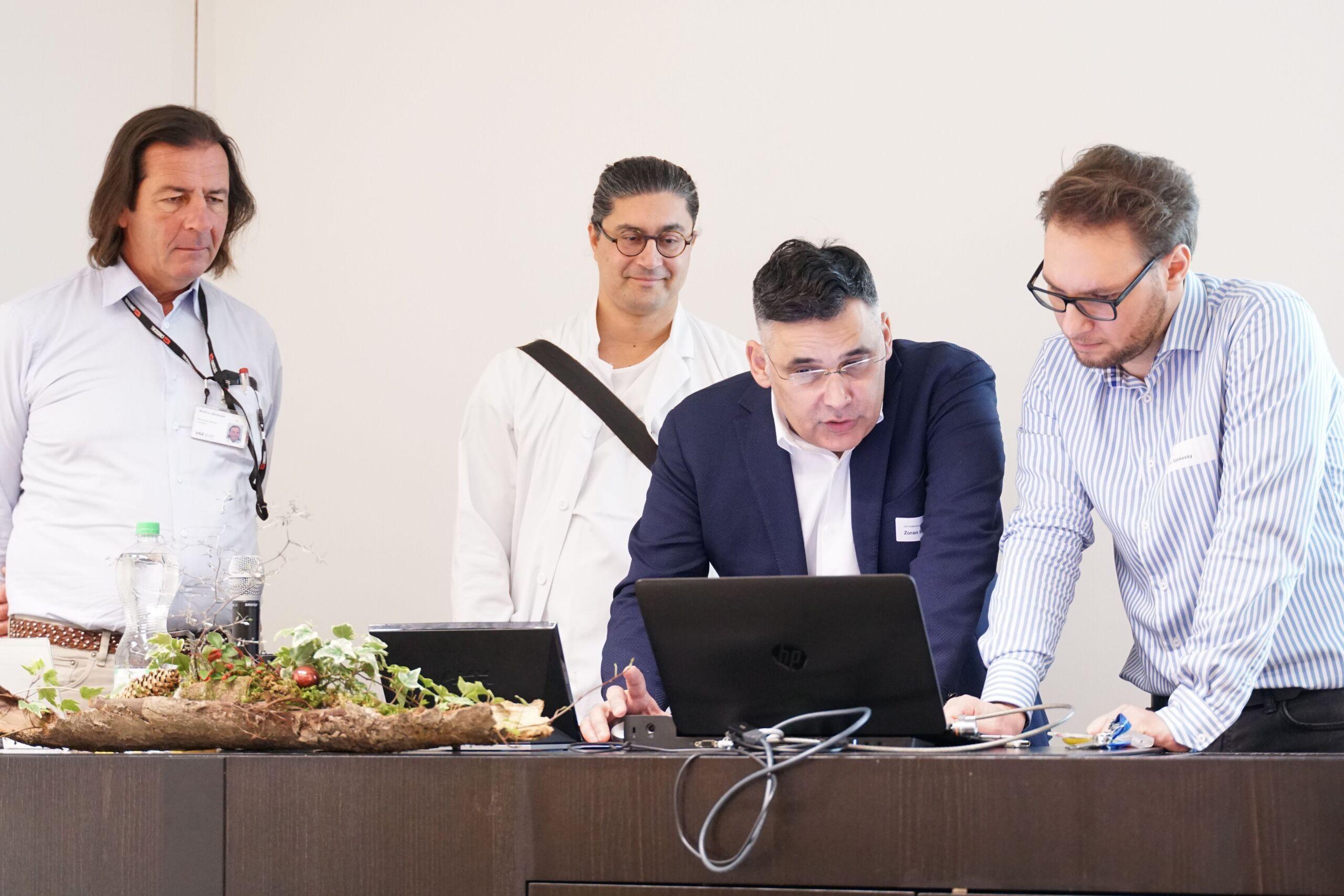 Vier Männer schauen auf einen Laptop