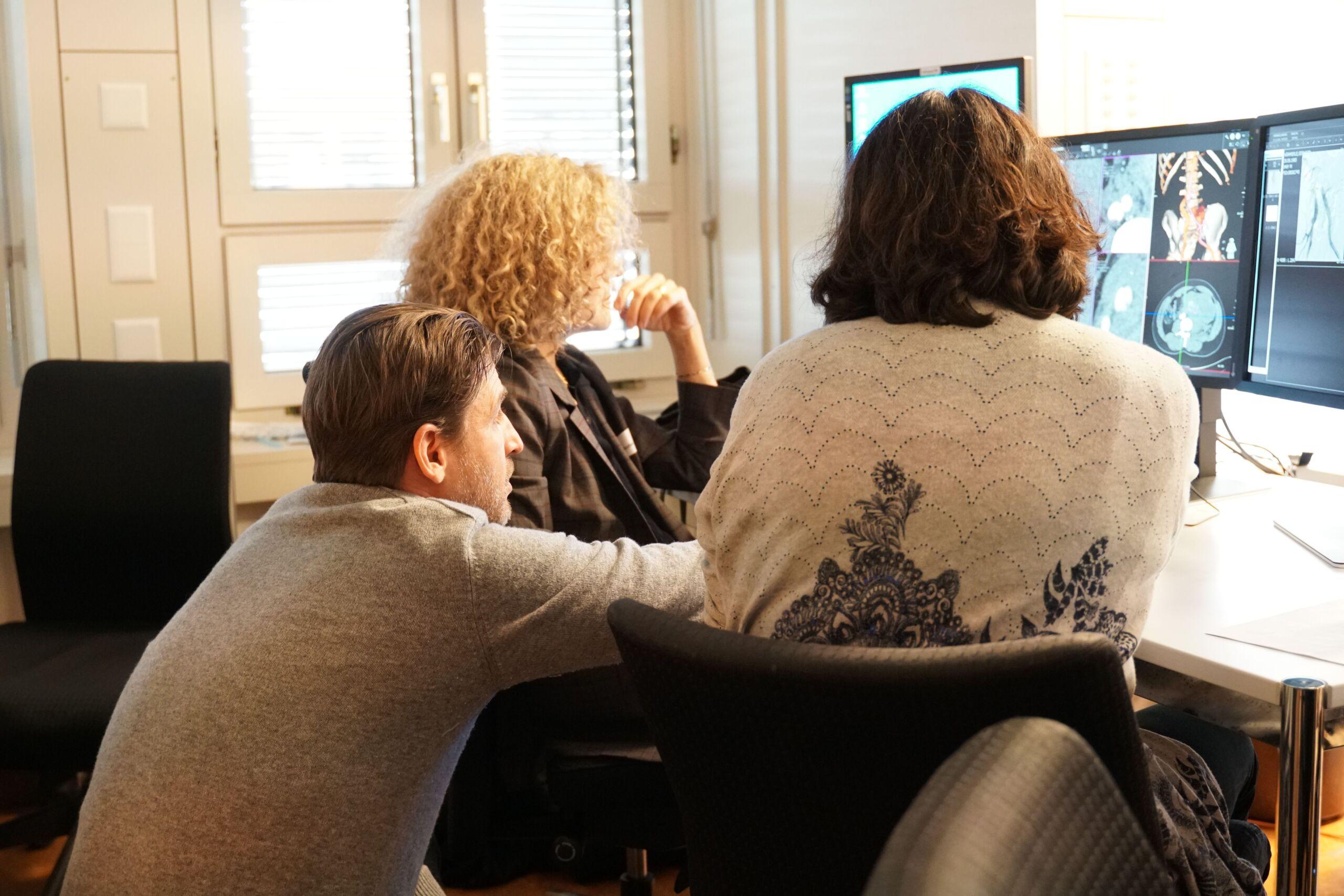 Drei Personen schauen sich Bilder vom Körperinneren an