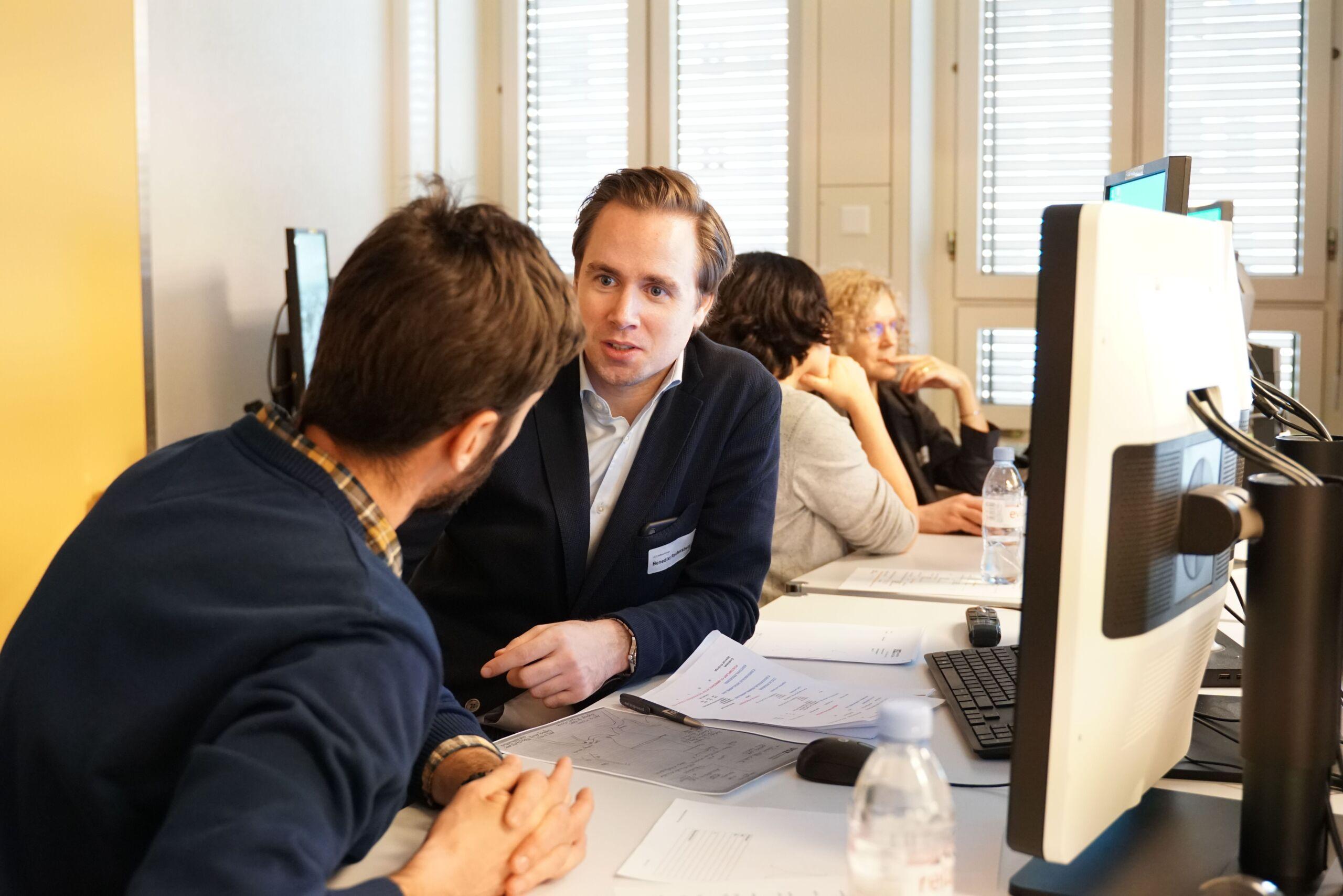 Zwei Männer und zwei Frauen diskutieren etwas und sitzen dabei vor Computern