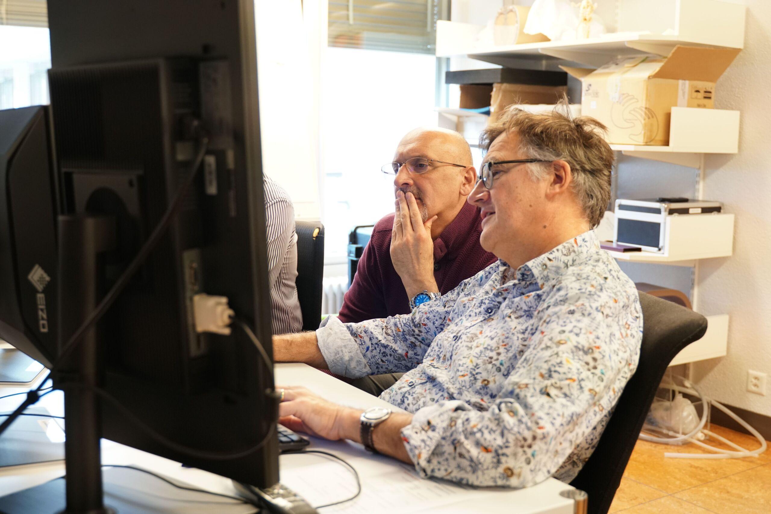 Zwei Männer sitzen an einem Computer und bereden etwas