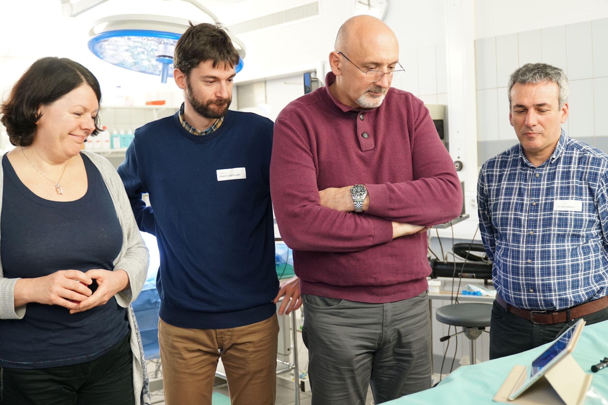 Drei Männer und eine Frau schauen sich eine Instruktion auf einem Tablet an