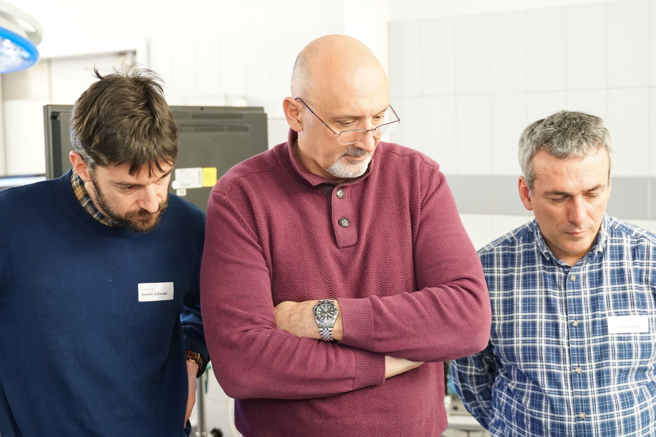 Drei Männer schauen bei etwas zu
