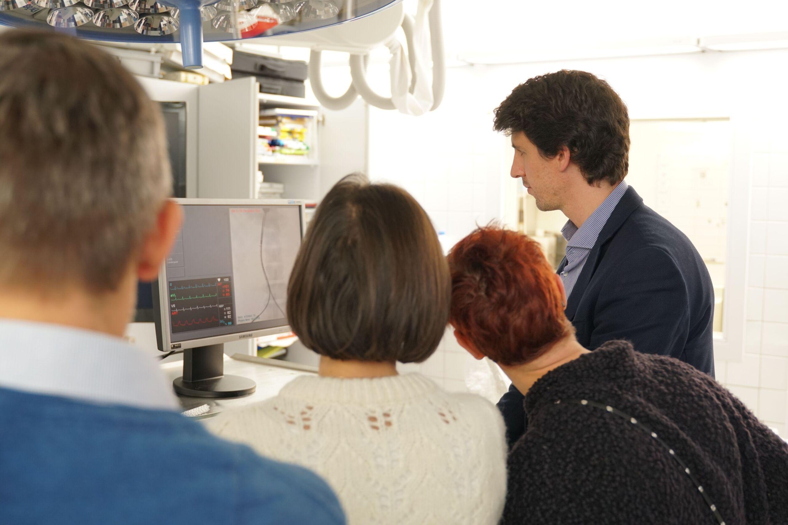 Vier Personen schauen sich eine Aufnahme auf einem Bildschirm an