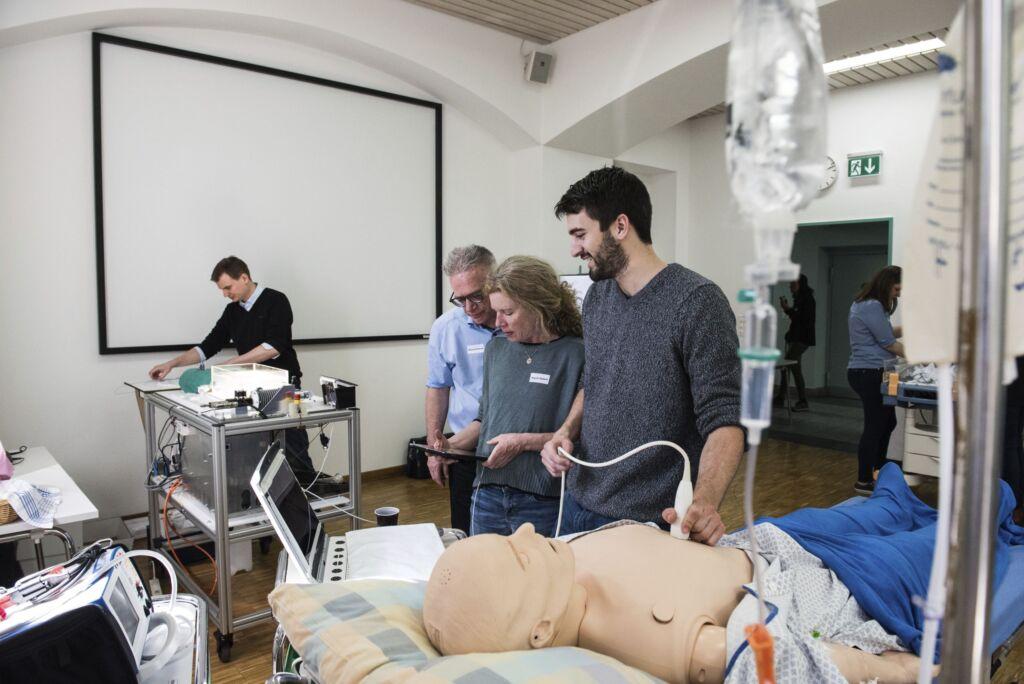 Drei Personen führen eine Ultraschalluntersuchung an einer Puppe durch