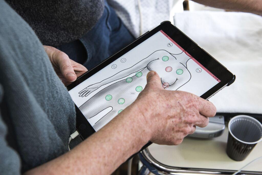 Tablet wird bedient und zeigt verschiedene Punkte bei der Puppe