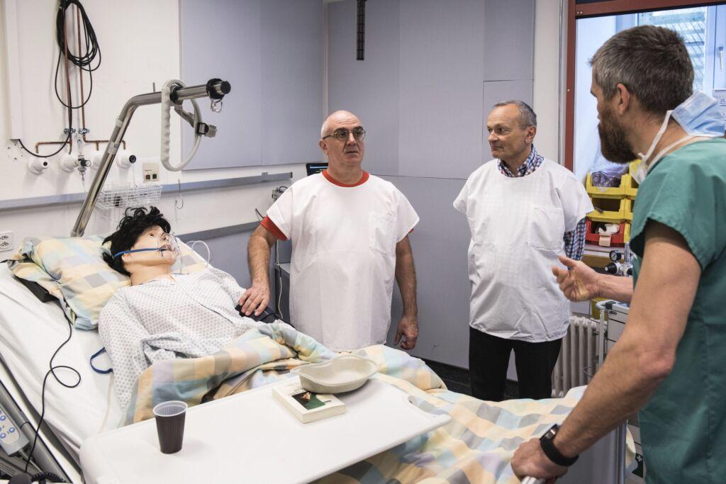 Drei Männer besprechen die nächsten Schritte bei der Simulation an einer Puppe