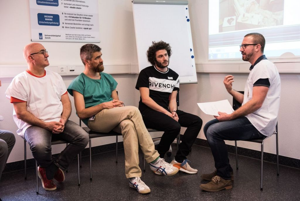 Ein Leiter und drei Zuhörer in einem Raum beim Briefing zur Simulation