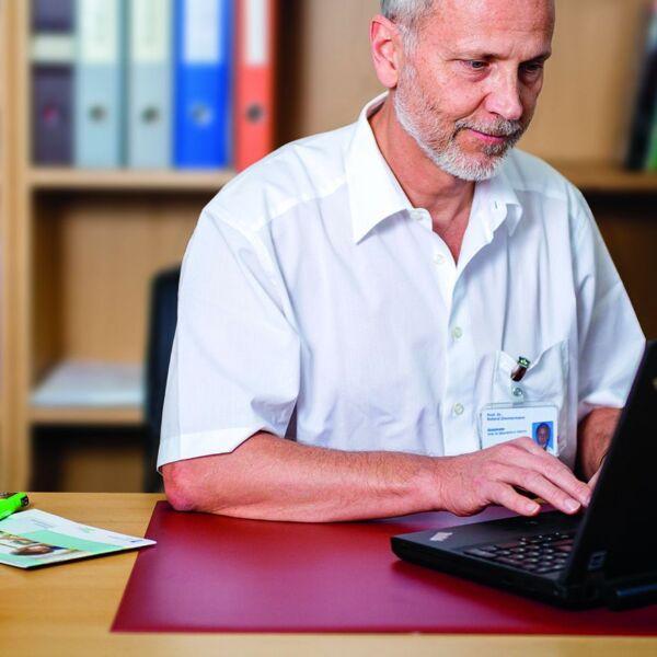 Ein Arzt sitzt in seinem Büro an einem Laptop