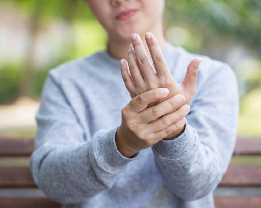 Eine Hand hält die andere, symbolisiert Handgelenksschmerzen
