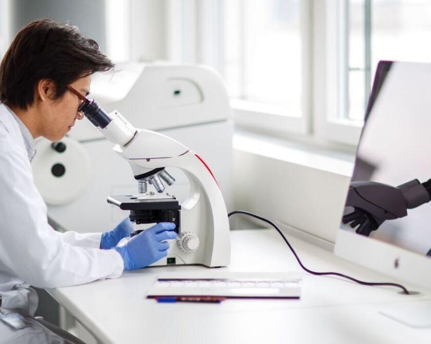 Forscher schaut durch ein Mikroskop