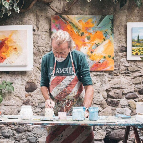 Älterer Mann steht vor einer Steinmauer und malt Gemälde mit einem Pinsel.