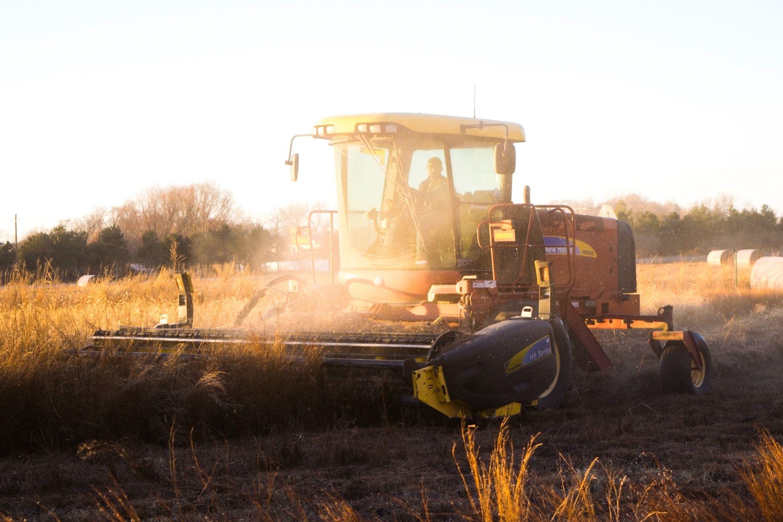 Ein Mähtraktor fährt bei Sonnenuntergang über ein Feld