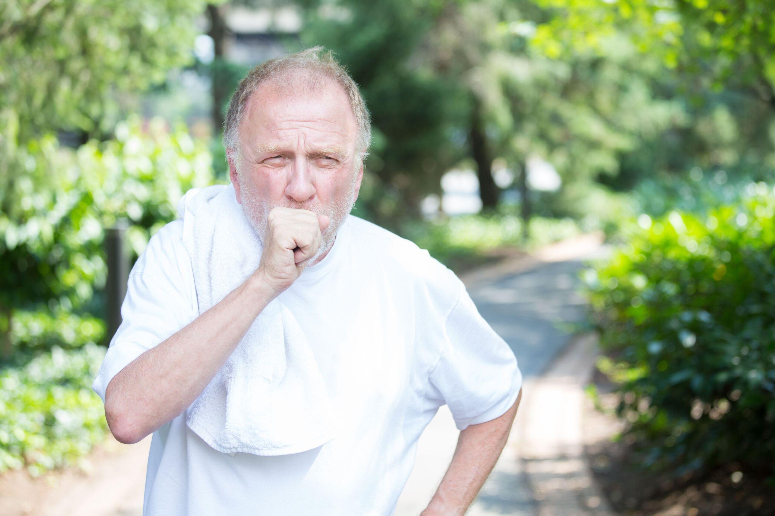 Ein älterer Mann hustet in einem Park in seine Hand