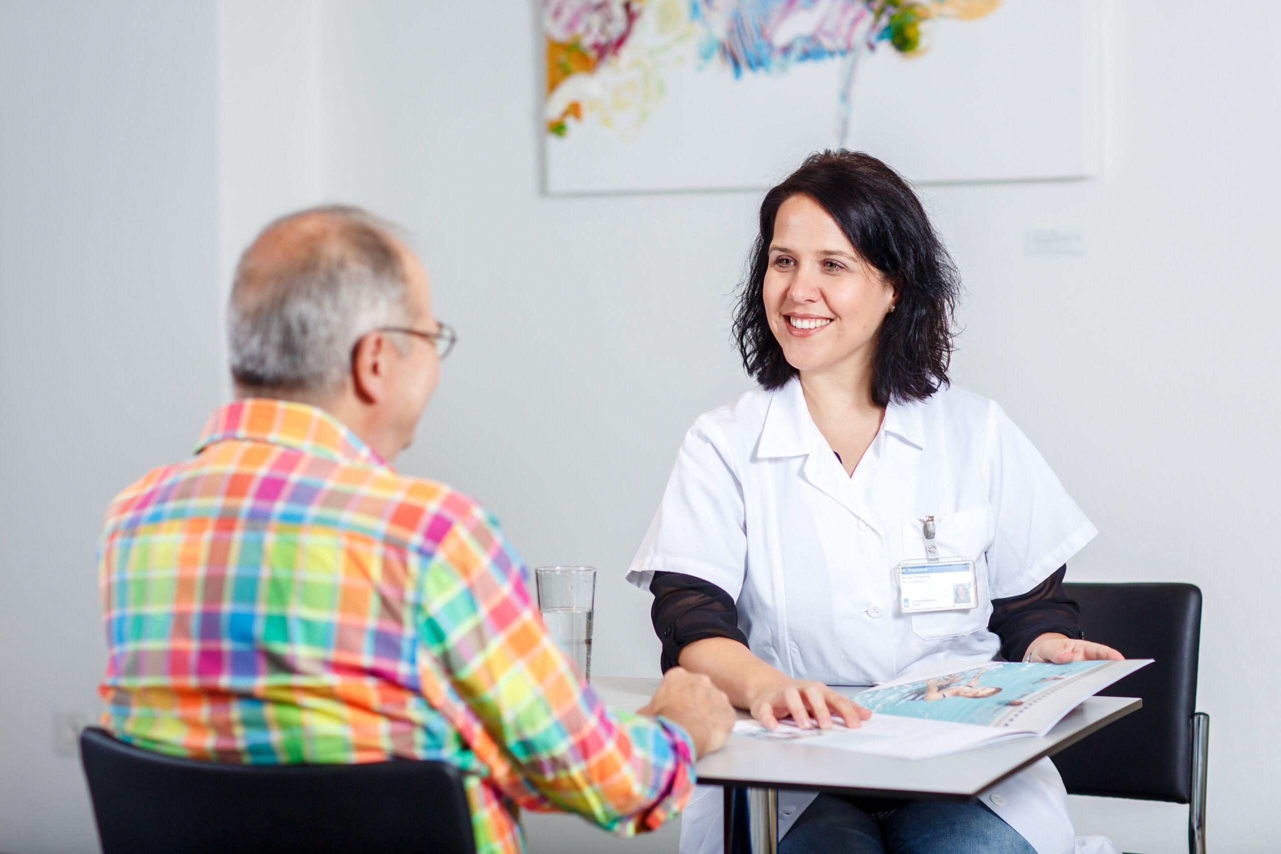 Eine Ärztin zeigt einem Patienten eine Broschüre