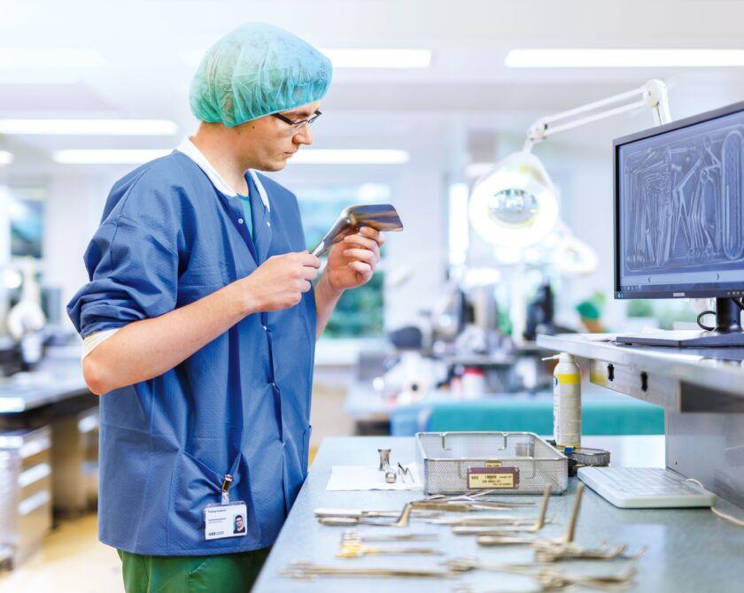 Ein Mann schneidet ein Teil zu, zur Operationsvorbereitung