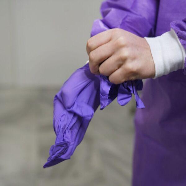 Eine Ärztin zieht sich Handschuhe an um sich auf einen Corona Patienten vorzubereiten