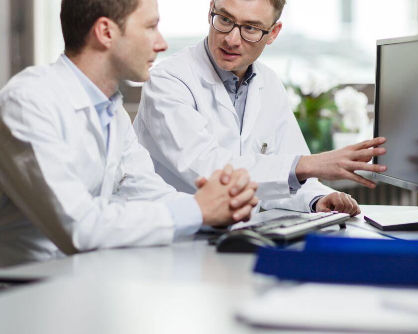 Zwei Männer schauen auf einen Bildschirm und besprechen etwas.