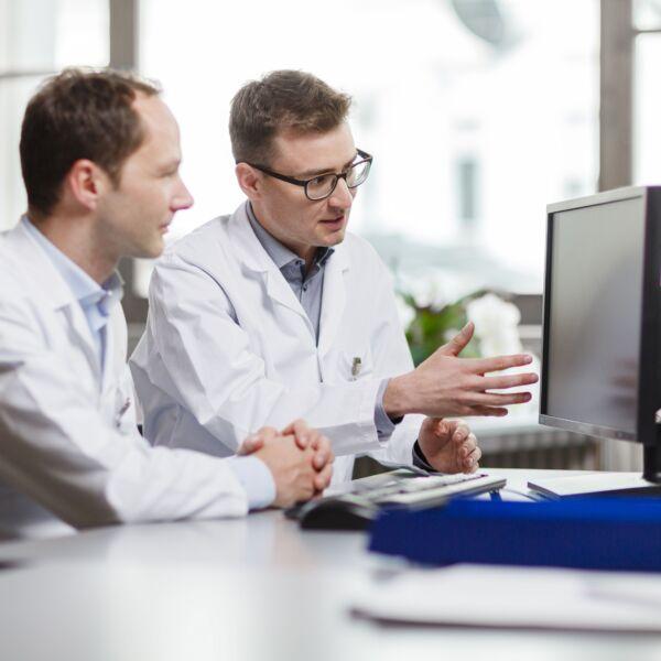 Zwei Ärzte besprechen etwas, das auf einem Computerbildschirm ersichtlich ist