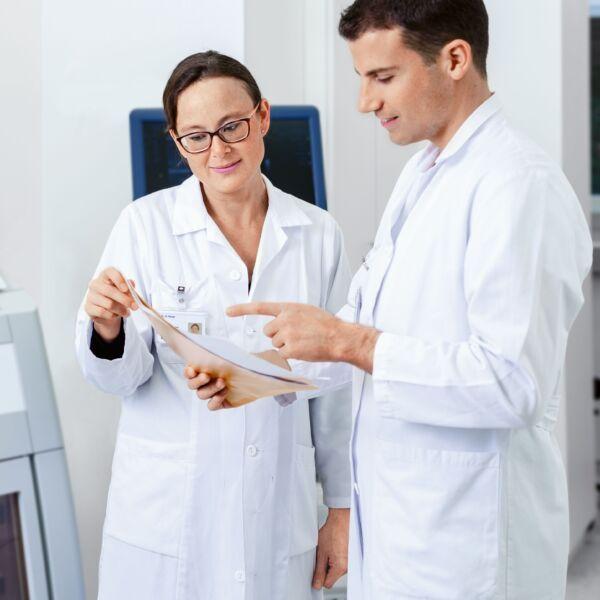 Ein Arzt und eine Ärztin besprechen ein Dossier