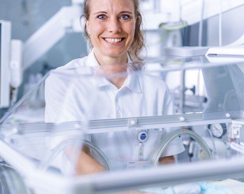 Eine Frau steht lächelnd vor einer Babystation