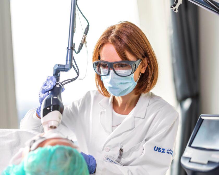 Eine Ärztin führt eine Laserbehandlung durch.