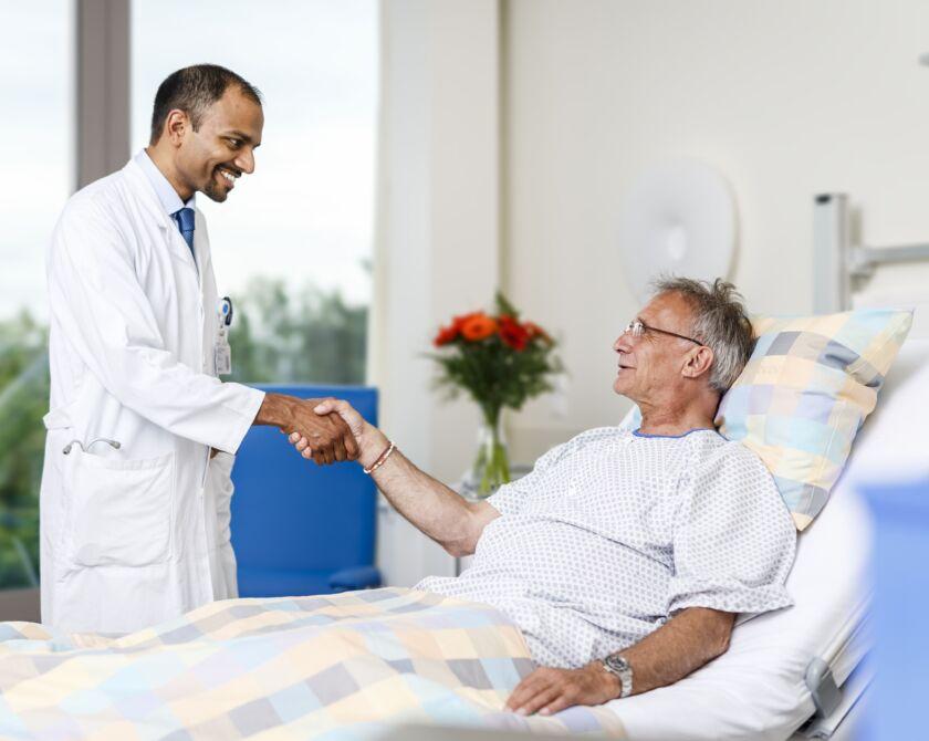 Ein Arzt begrüsst einen Patienten an seinem Patientenbett