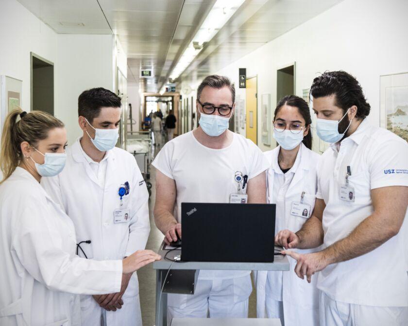 Ärztliches Fachpersonal schaut auf einen Laptop und diskutiert.