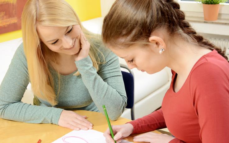 Eine junge Frau malt etwas auf einem Papier und ihre Therapeutin beobachtet sie dabei