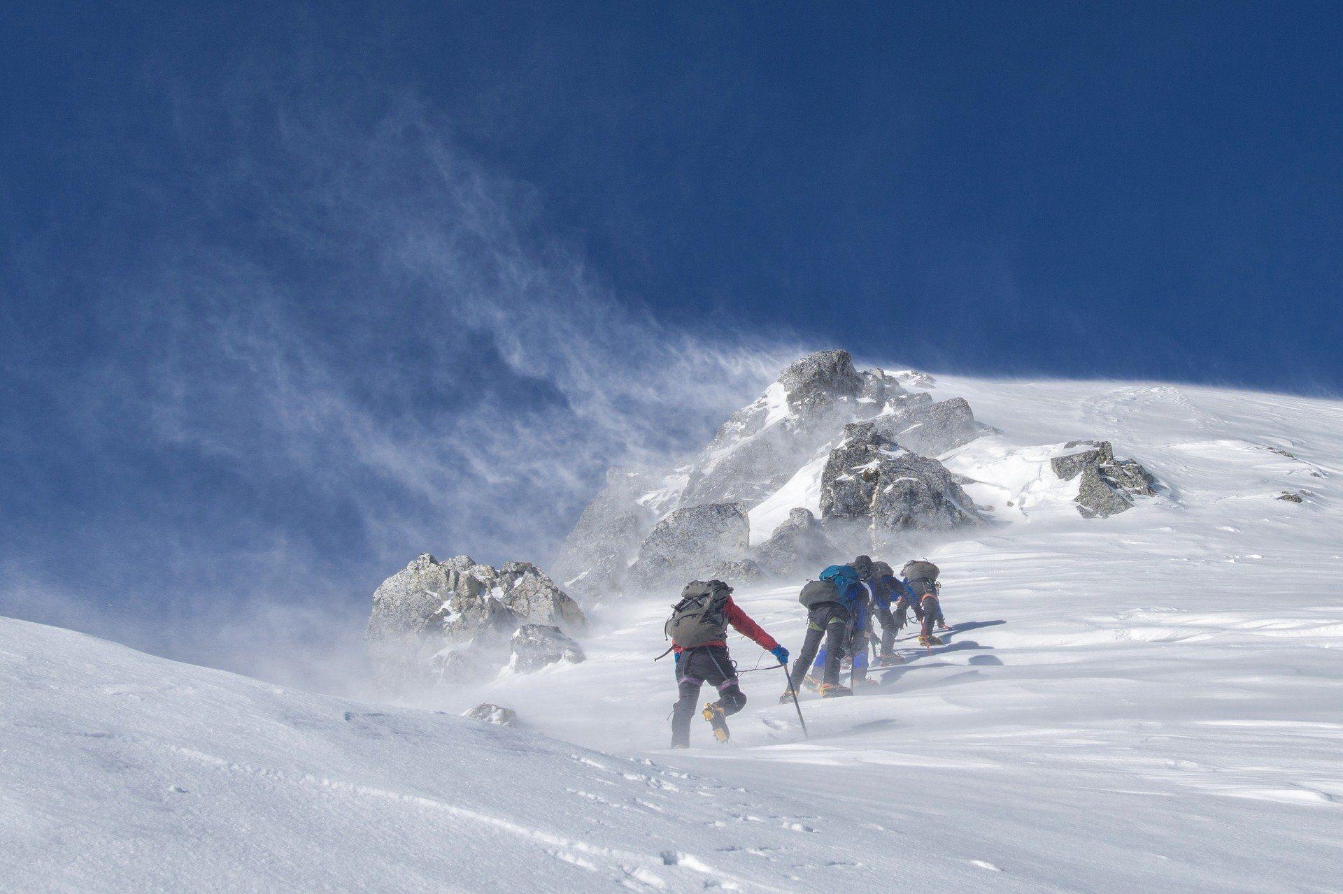 Vier Bergsteiger klettern einen Berg hoch