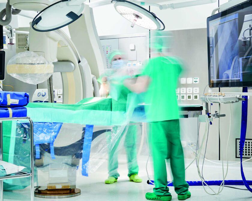 Zwei Personen bereiten eine Maschine für eine Untersuchung vor
