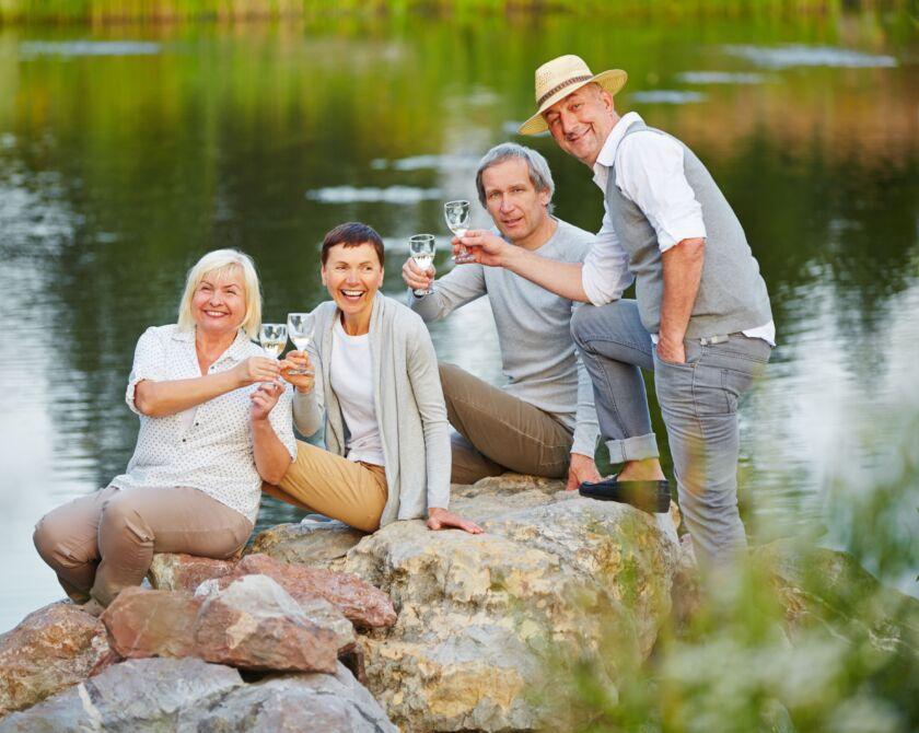 Zwei Frauen und zwei Männer geniessen ihre Zeit an einem See mit Wein