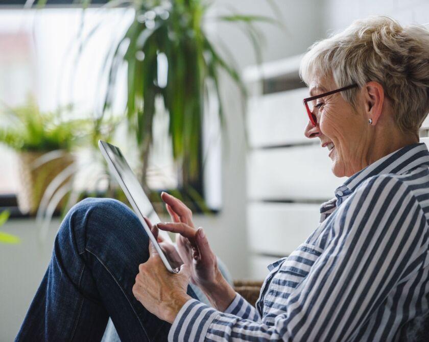 Eine ältere Frau sitzt am Boden und bedient lächelnd ein Tablet