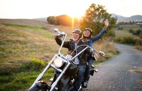 Ein Mann mit seiner Frau fahren auf einem Motorrad durch eine Landschaft bei Sonnenuntergang