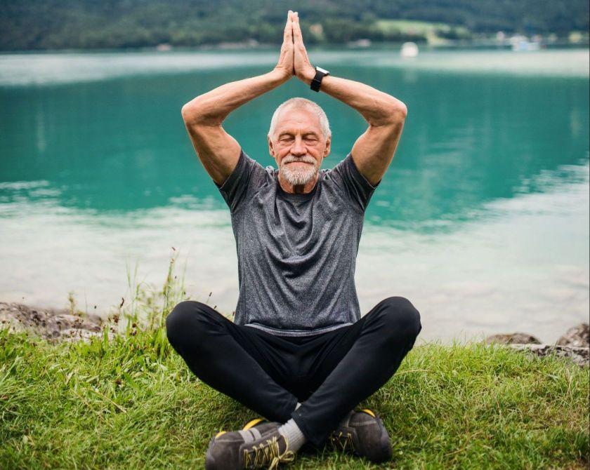 Ein Mann sitzt vor einem See im Gras und hält eine Yogaposition