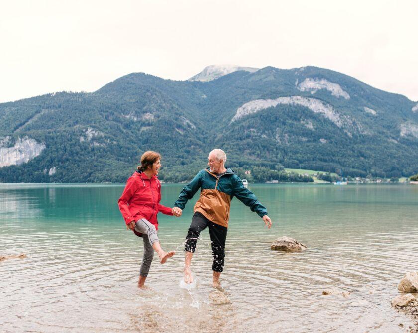 Ein älteres Ehepaar spritzt glücklich mit den Füssen Wasser aus einem See