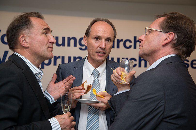 Drei Männer diskutieren während eines Aperos