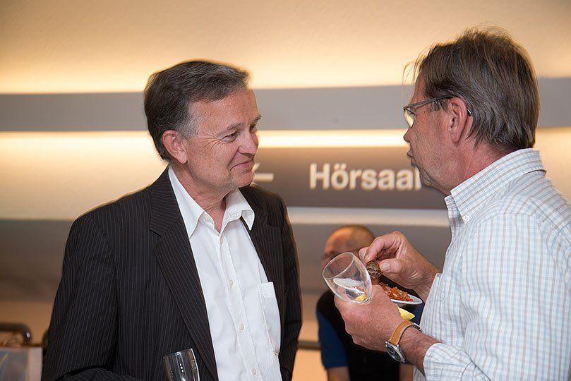 Zwei Männer reden an einem Apero miteinander