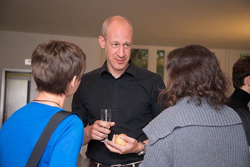 Ein Mann diskutiert mit zwei Frauen bei einem Apero