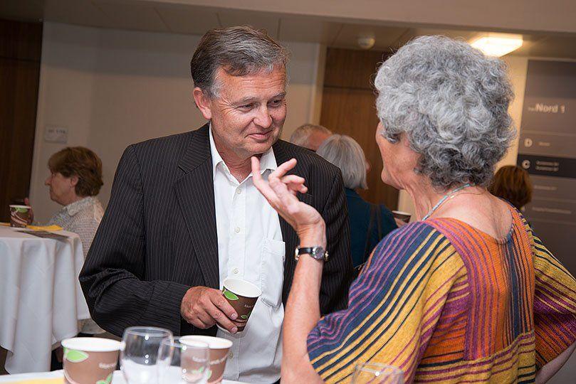 Ein Mann und eine Frau reden an einem Stehtisch miteinander