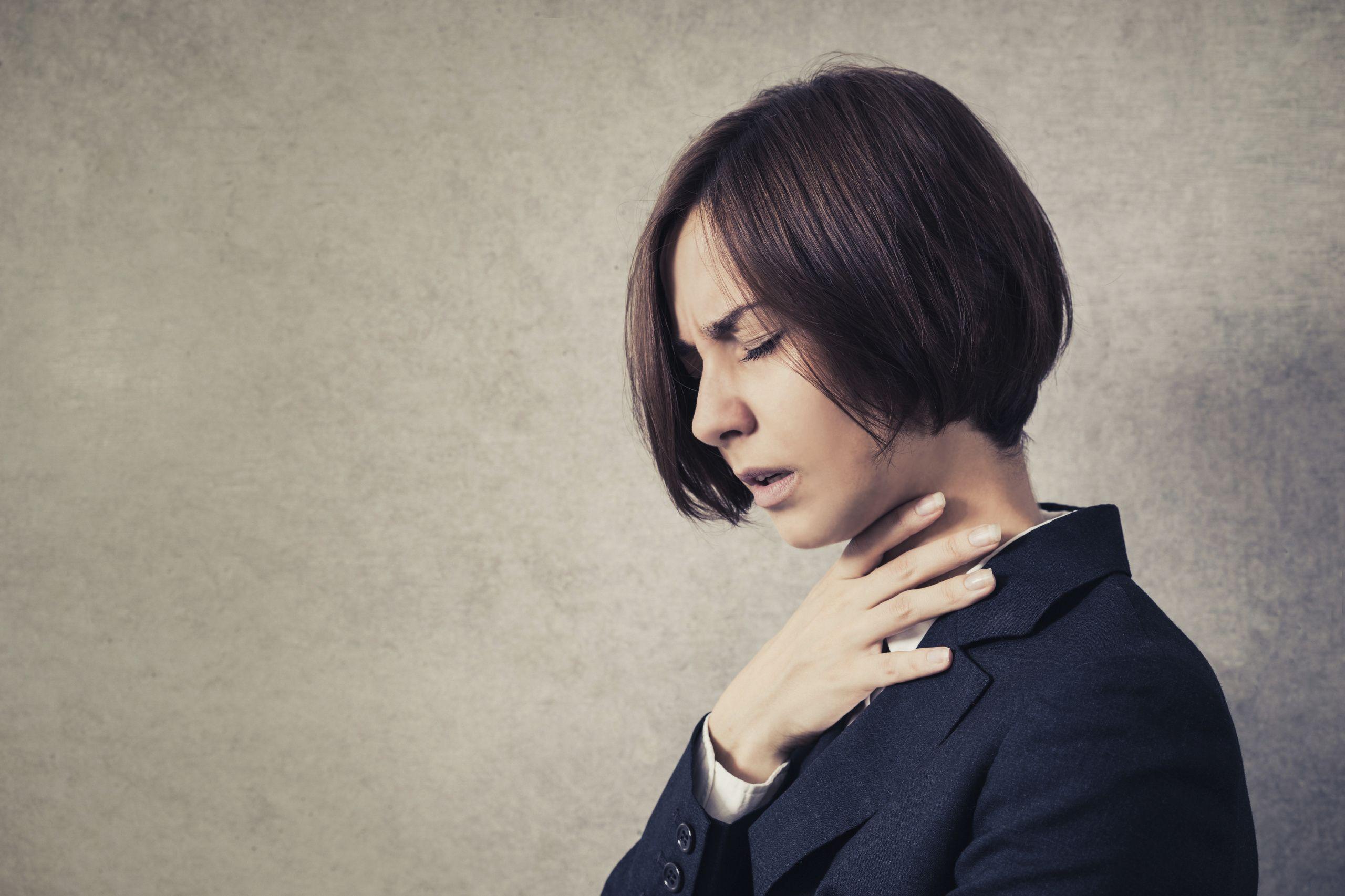 Eine Frau fasst sich an den Hals aufgrund von Halsschmerzen oder Atemnot